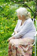 The grandmother in  garden under a blossoming apple-tree - stock photo