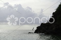 Jumping Off Rock Silhouette Stock Photos