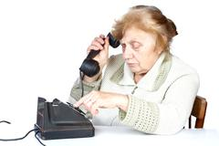 The old woman dials  number of phone - stock photo
