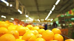 Oranges and unrecognizable customers in supermarket. Slow motion video Stock Footage