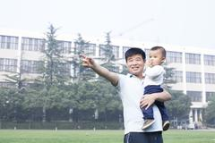Chinese father and son pointing afar - stock photo