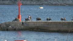 People sitting on benches on the dock near Fortress Saint Ivan in Dubrovnik Stock Footage