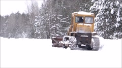 Clearing snow from the road. Crawler Tractor grader clears snow from the road. - stock footage