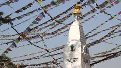 A small stupa on the sky background with flags Stock Footage