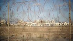Barbed wire security fence, buildings in background, shallow DOF Stock Footage