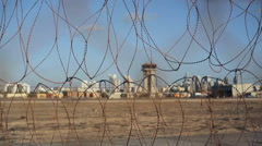Barbed wire security airport fence, focus pull control tower, shallow DOF Stock Footage