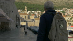 View of a couple walking in the port near moored boats in Dubrovnik, Croatia Stock Footage