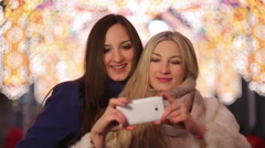 A brunette and a blonde doing a selfie on the background of festive city lights Stock Footage