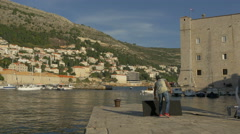 View of a man touching a black board and leaving the port in Dubrovnik, Croatia Stock Footage