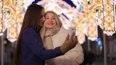 Two girls doing a selfie on the background of festive city lights. - stock footage
