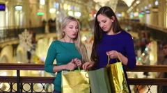 Two girls, a blonde and a brunette, consider their purchases at the Mall. Stock Footage