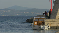 Moored boat and people on shore near Saint Ivan fortress in Dubrovnik, Croatia Stock Footage