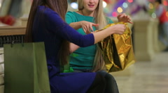 Two girls, a blonde and a brunette, consider their purchases at the Mall. - stock footage