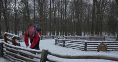 Man Picks Up a Snow From a Wooden Benches Ground Throws the Snow To Camera Man Stock Footage