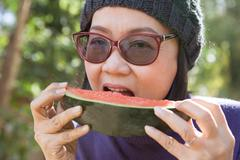 close up face of young woman earting water melon - stock photo