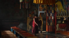 A boy with a censer in a Buddhist monastery Stock Footage