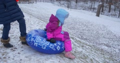 Little Girl Rides From Hill on Inflatable Sledge Snowtubing She Almost Knocks Stock Footage