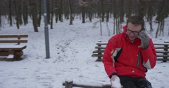 Man Sitting on Log Fence Throws Handful of Snow Up Talking by Phone Man in Red Stock Footage