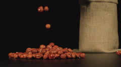 A hazelnuts fall in a pile on a table near a bag - stock footage