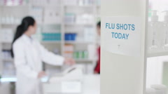 4K Flu shots notice in a chemist shop with worker serving customer in background Stock Footage