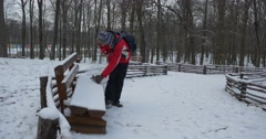 Man Cleans The Bench From a Snow Sits Talking Mobile Phone Puts a Phone into Stock Footage