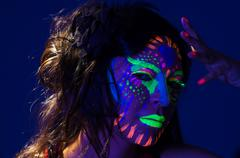 Headshot woman wearing awesome glow in dark facial paint, blue based with other Stock Photos
