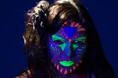 Headshot woman wearing awesome glow in dark facial paint, blue based with other - stock photo