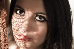 Headshot brunette model using patterned shadows as artistic effect on face while - stock photo