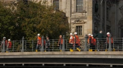 Large group of construction workers cross a bridge Stock Footage