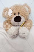 Teddy Bear Laying in Bed - stock photo