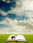 Binocular and book on grass, Vision from education concept - stock photo