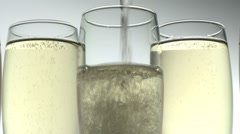 POURING CHAMPAGNE INTO THREE GLASSES Stock Footage