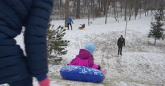 Snowtubing Little Girl Rides on Inflatable Sledge Mom Pushes the Sledge From Stock Footage