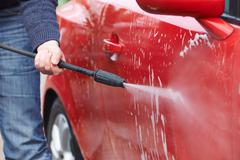 Man Washing Car With Pressure Washer - stock photo