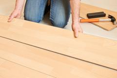 Man Laying Laminate Flooring - stock photo