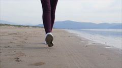 Low section of woman's feet walking on beach Stock Footage