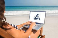 Composite image of pretty brunette using laptop on deck chair Stock Photos