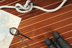 Nautical divider on a chart, rope and binoculars - stock photo