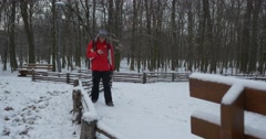 Man is Talking by Phone Walking to Bench Sits Wooden Bench Covered With Snow Stock Footage