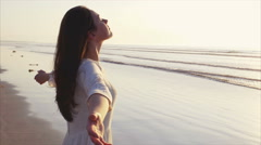 Woman standing with arms outstretched on shore - stock footage