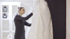 Woman chooses wedding gown at bridal boutique Stock Footage