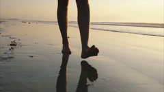 Low section video of barefoot woman walking on wet sand during sunset - stock footage