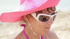 Stylish lady in a hat and sunglasses smiles at sea and eats watermelon Stock Footage