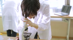 Female scientist looking into microscope mid shot Stock Footage