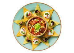 Tortilla chips arranged around a bowl of salsa - stock photo