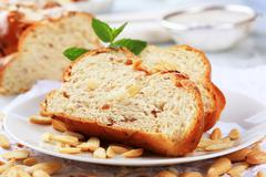 Slices of sweet braided bread and blanched almonds - stock photo