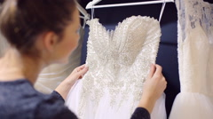Girl chooses wedding gown at bridal boutique Stock Footage