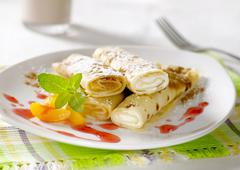 Rolled up crepes filled with sweet fillings - stock photo