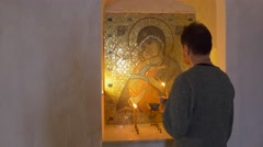 A Man Prays, Bows Down, and Crosses Himself, at Icon of Saint Mary With Jesus Stock Footage