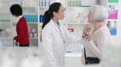 4K Worker in a chemist shop assisting mature lady. - stock footage